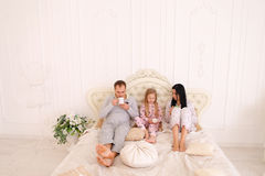 Happy family drinks tea or coffee in pajamas smiling and looking Stock Photos