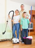 Happy family dusting in home Stock Image