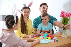 Happy family with Easter eggs at home stock photography