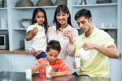 Happy family eating biscuits and drinking milk Stock Images
