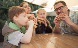 Happy family eating burgers sitting at a table in a cafe stock photo