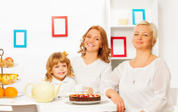 Happy family eating cake and drinking tea. Happy family mother father and granddaughter eating cake by the table with smile Royalty Free Stock Images