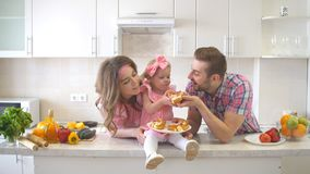 Happy Family Eating Cake in the Kitchen stock photo