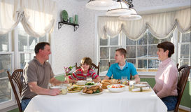 Happy family eating at dinner table Stock Images