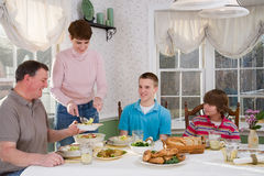 Happy family eating at dinner table Stock Photo