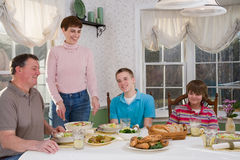 Happy family eating at dinner table Royalty Free Stock Photos