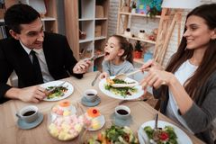 Happy family eating dishes at table together. Parents with their daughter gathered at table. royalty free stock images