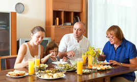 Happy family eating fish with vegatables at home Stock Photography