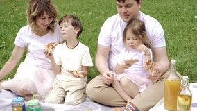 Happy family eating pizza and having fun at the picnic. Happy family eating pizza and having fun at the picnic stock footage