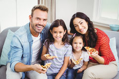 Happy family eating pizza while sitting on sofa Royalty Free Stock Photo