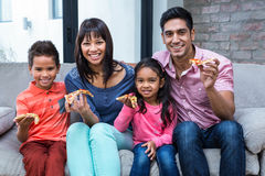 Happy family eating pizza on the sofa Stock Images