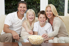 Happy Family Eating Popcorn Watching Television. An attractive happy family of mother, father, son and daughter sitting on a sofa at home watching a film or Stock Photos
