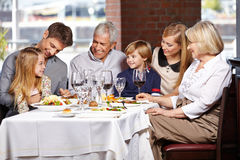 Happy family eating in restaurant. Happy family with children and seniors eating out in a restaurant stock photo