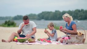 Happy family eating watermelon on the beach stock footage