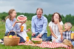Happy family eating watermelon at a picnic. Picnic in the meadow or park. Young friends and their children in nature.  stock photography