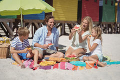 Happy family eating watermelon while sitting together at beach Royalty Free Stock Photo