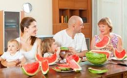 Happy family eating watermelon Stock Photos