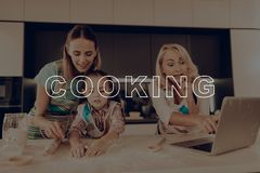 Happy Family Enjoy Cooking . Woman Help Girl. Happy Family Enjoy Cooking. Woman Help Girl. Little Girl Hold Rolling Pin. Grandmother with Laptop. Grandmother royalty free stock images