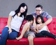 Happy family enjoy quality time on red sofa. Happy Asian family enjoy relaxing time on red sofa with grey background Royalty Free Stock Photos