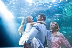 Happy family enjoying behing a fish tank Stock Photos