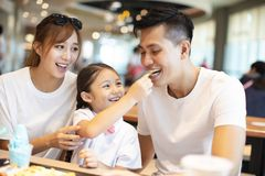 Happy family enjoying dinner in restaurant. Stock Photos
