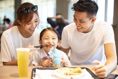Happy family  enjoying dinner in restaurant. Royalty Free Stock Image