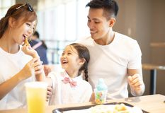 Happy family enjoying dinner in restaurant. Royalty Free Stock Photography