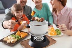 Happy family enjoying fondue dinner at home royalty free stock photos