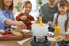Happy family enjoying fondue dinner at home stock photos