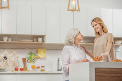 Happy family enjoying friendly talk in kitchen. I baked this sweet pastry for you. Caring young women is treating her mother with bun and tea. She is standing Royalty Free Stock Photos