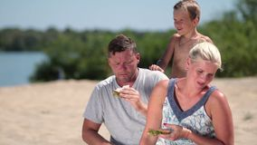 Happy family enjoying lunch on the beach stock video footage