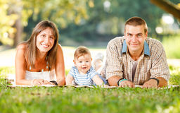 Happy Family Enjoying In The Park. Beautiful happy family lie on the grass in park Stock Photos