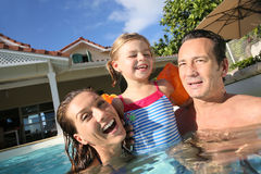 Happy family enjoying summer holidays in swimming pool Stock Image