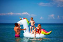 Happy family enjoying summer vacation, having fun in water on inflatable unicorn. Happy family enjoying summer vacation together, having fun in water on Stock Photo