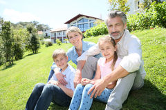 Happy family enjoying sun in the garden. Happy family sitting in home private garden Royalty Free Stock Images