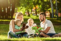 Happy family enjoying sunny day playing in the park. Happy family enjoying sunny day, parents playing with children on a green grass in the park Stock Images