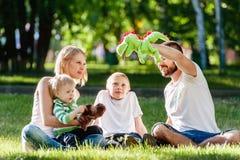 Happy family enjoying sunny day in the park. Happy family enjoying sunny day playing together in the park Stock Image
