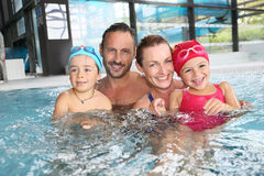 Happy family enjoying in swimming pool. Portrait of family having fun in public indoor swimming-pool Royalty Free Stock Images