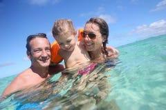 Happy family enjoying swimming in the sea Stock Photos