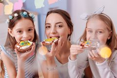 Happy family enjoying their hand made desserts. Three beauties. Attractive female person expressing positivity while spending day with her daughters stock photo