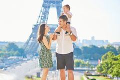 Happy family enjoying their vacation in Paris, France. Happy family of three standing in front of the Eiffel tower and enjoying their vacation in Paris, France Royalty Free Stock Photos