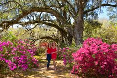 Happy family enjoying time together in blooming garden. Happy smiling mother and daughter enjoying beautiful spring day in the garden. Azaleas in bloom under stock photography