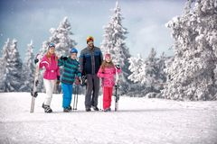 Happy family enjoying in winter vacation in mountains. At ski resort Royalty Free Stock Photo