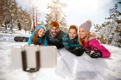 Family enjoying winter vacations in mountains and making selfie Stock Photos