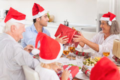 Happy family exchanging christmas gifts. Happy family exchanging gifts at christmas time around the dinner table Stock Images