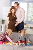 Happy family expecting baby. Happy family with two daughters expecting baby, mother and father hugging each other Stock Images