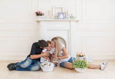 Happy Family Expecting New Baby. Pregnant Woman with Husband kiss the little son. Family portrait against the background of a fireplace Royalty Free Stock Image