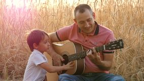 Free Happy Family: Father And Son Are Resting, Sitting On The Background Of A Wheat Field. Father And Child Play Guitar And Royalty Free Stock Images - 156190529