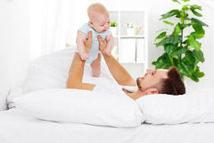 Happy family father and baby on bed Royalty Free Stock Photography