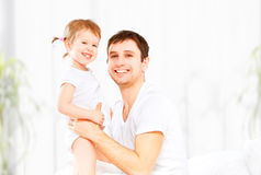 Happy family father and baby  daughter playing in bed Stock Photo